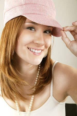 smoothen: high fashion portrait of a caucasian girl with happy expression wearing pink hat. retouched to smoothen skin