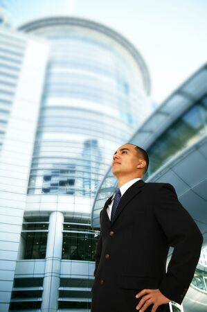 fulfill: a succesful business man standing in front of tall modern office building