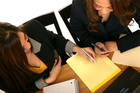 two business women writing or discussing something that is on the yellow notepad. could be business plan, financial plan, etc