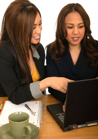 инструкция: two business women working together with laptop. one giving instruction to the other