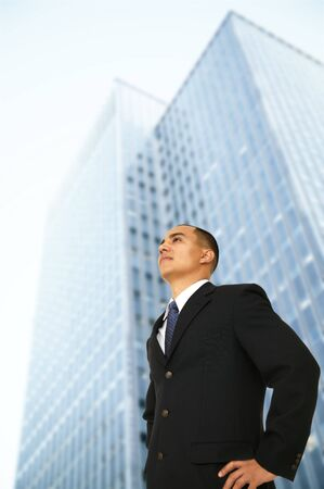 fulfill: business man standing outdoor in front of tall squared business building