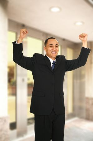 a man raised his man with joyful expression when coming out from office building because he just got a job Stock Photo