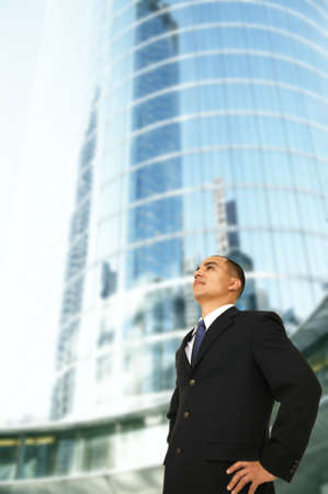 fulfill: an architect or designer or business owner or ceo of a big company standing by tall contemporary office building where he work
