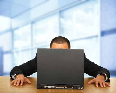 a man staring at laptop in his big contemporary office space
