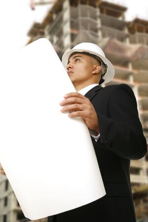 a man wearing hard hat and business suit looking at floor plan in front of under construction building