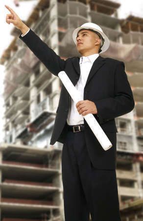 a construction worker with hard hat pointing at somewhere, holding roll of floor plan with building under construction behind him Stock fotó