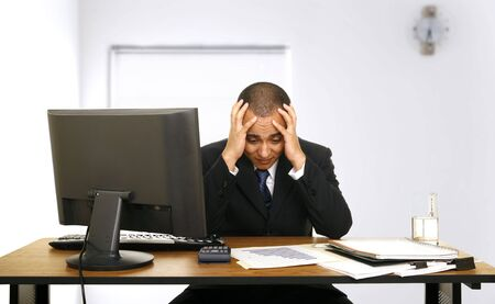 an employee stressed out holding his head looking at sales chart