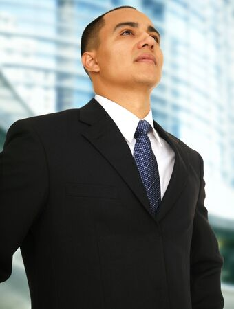 successful business man standing and looking up with abstract building background
