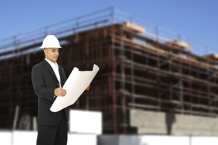 a man wearing suit and hard hat looking at floor plan and building under construction behind him photo
