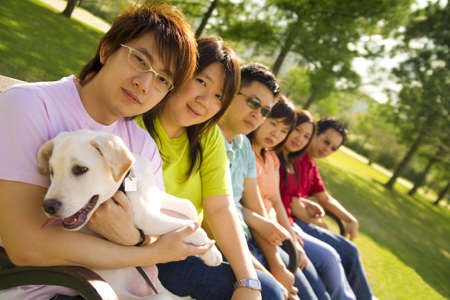 a group of asian friends sitting down on a bench outdoor with puppy labrador looking at camera with happy expression photo