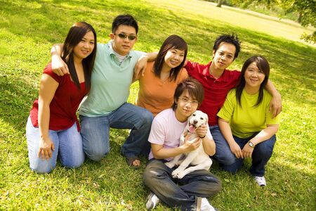 a group of asian friends posing casual on grass outdoor in a bright day photo