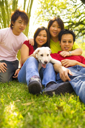 a group of four asian teens sitting on grass with puppy labrador photo