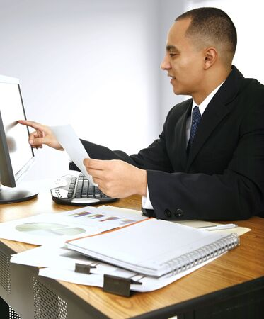 a business man looking at computer screen and smiling in his office Stock Photo - 2809271