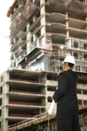 executive apartment: a man pointing at a building under construction giving instruction to other worker