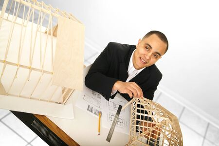 shot of an architect designer working in his office. he is looking up to the camera