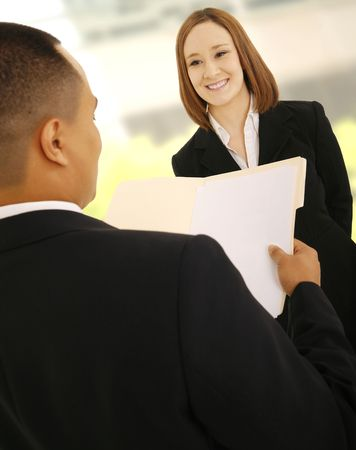 teammate: business man looking at empty folder as if he is reviewing his woman teammate work. Stock Photo