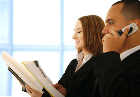 two business people working in office environment. the man is on the phone while the woman is smiling and reading empty folder Stock Photo