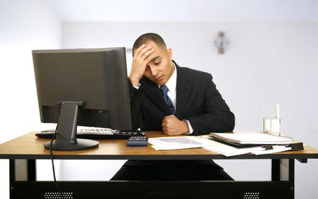 an employee stressed out and still working in his office with a little clock behind him showing a time to get off