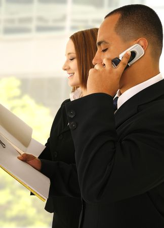 two business people busy standing working and holding folder. the business man is on the phone and the woman is smiling Stock Photo - 2891152