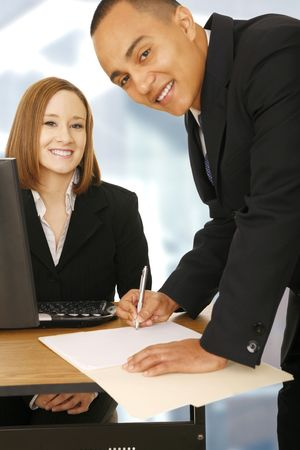 technology deal: shot of business man bend over to sign an empty paper, focus on the woman smiling on the background. concept for business deal, contract, or team work