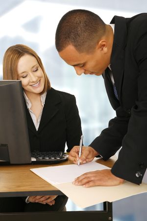 business woman looking at business man bend over to sign an empty paper on table. focus on the woman. perfect concept for business deal and team work Stock Photo - 3004244