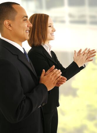 presentaion: two business people clapping hand while looking to the side as if they are listening to presentaion
