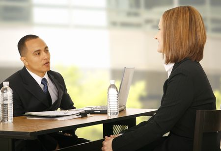 two business people sit across each other and discussing work. focus on the woman. perfect concept for business talk, selling, or team work
