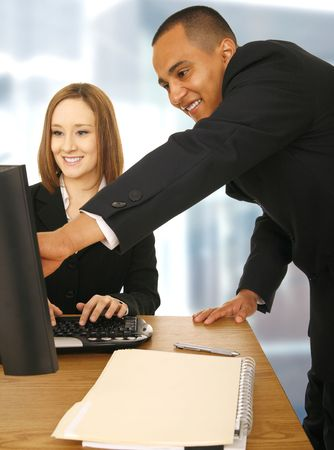 business man showing and pointing at screen while his coworker looking at the computer screen and smile. concept for mentor, supervisor, office related, and team work