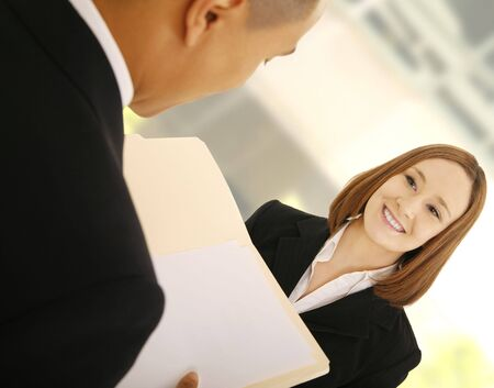 two business people working as a team discussing work. the man is holding folder and the woman is smiling photo