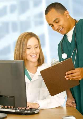 two medical people looking at same clip board and smiling. the woman is sitting down and the nurse is standing photo