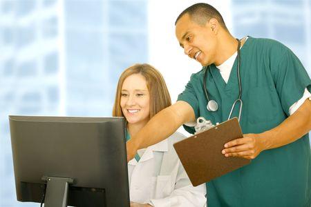 uniforme medico: enfermera en uniforme m�dico apuntando a la pantalla del ordenador con su ayudante de sentarse. ambos mostrando feliz expresi�n. concepto para el trabajo en equipo