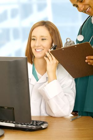 doctor calling on the phone and looking at her computer while her assistant on her back holding clip board. medical concept in modern office