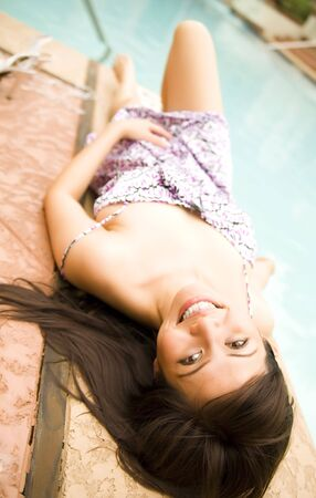shot of happy beautiful brunette laying by pool side Stock Photo - 3113248