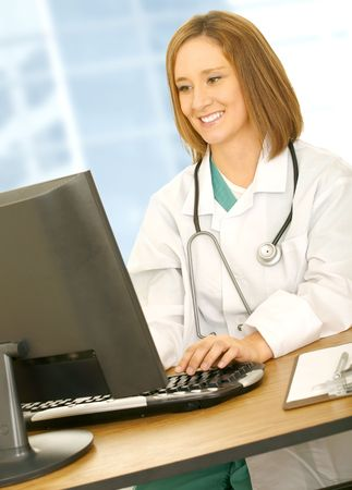 medical field: busy doctor smiling and typing on computer. concept for medical field and modern office