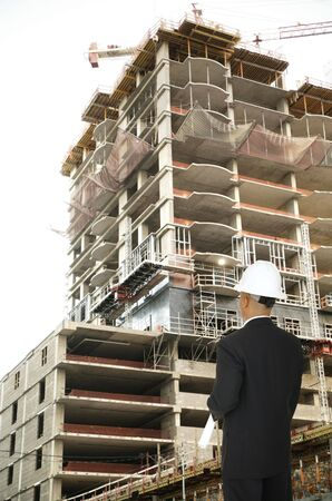 a man wearing hard hat and standing looking at building outdoor under construction Фото со стока