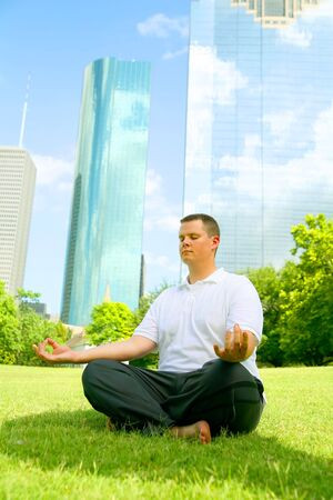 handsome caucasian man meditate outdoor in a park with downtown building in the background. concept for yoga or wellbeing Stock Photo - 3255908