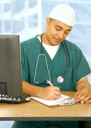 happy nurse or doctor in medical uniform writing report on clip board, showing happy expression photo