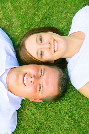 two caucasian couple lay down on grass looking up