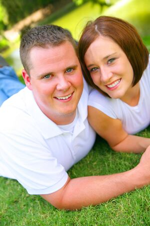 happy caucasian couple laying on grass and holding hand with smile. concept for happiness and Stock Photo - 3261365