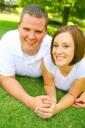 soulmate: happy caucasian couple laying on grass and holding hand with smile. concept for happiness and  Stock Photo