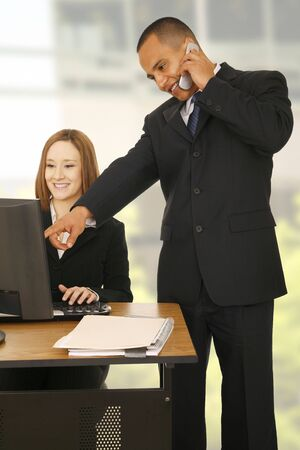 looking for work: a man on the phone while pointing at computer screen while the other business woman looking at the screen and smiling. concept for business communication, or team work