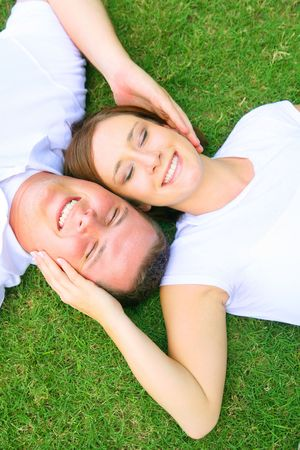 two caucasian couple lay down on grass and sleeping or relaxing. concept for happiness and