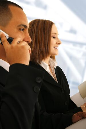 business man on the phone talking and business woman looking at folder. concept for business hour or working people