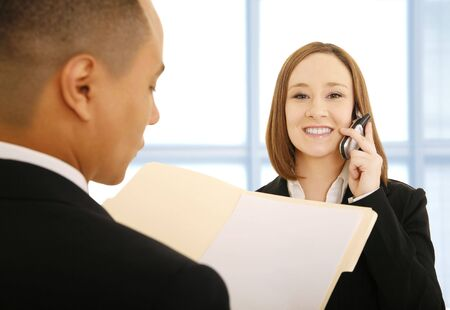 reviewing: business people looking busy. the woman on the phone and looking at camera smiling, the man is reviewing work or folder