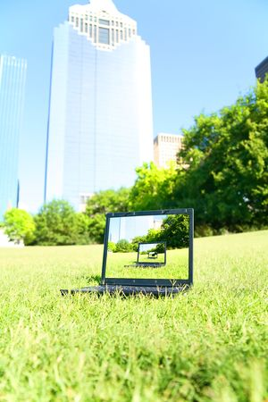 a computer sit on a grass with downtown building on the background. computer screen showing repeated pattern of the picture. concept for business, computer or technology Archivio Fotografico