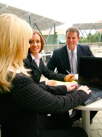 two business people paying looking at their coworker typing on laptop with blank screen photo