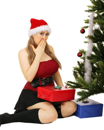 mrs santa claus sitting by christmas tree holding a gift with surprised expression 免版税图像