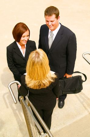 three business people having informal chatting under stair. the business man is holding his suitcase photo