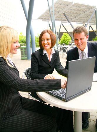 business team working. one blond woman showing laptop to her associates Stock Photo - 3413192