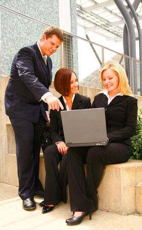 two business women sitting outdoor holding laptop and another business man pointing at the laptop Фото со стока